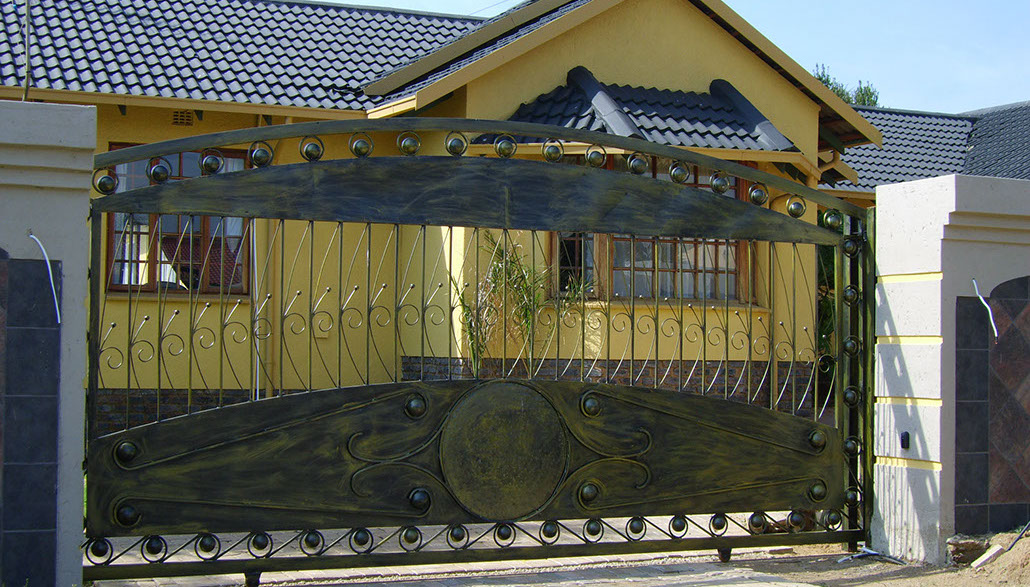 Wrought iron scrolls and sheet metal sliding gate